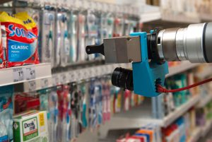 A robotic arm in front of a supermarket shelf