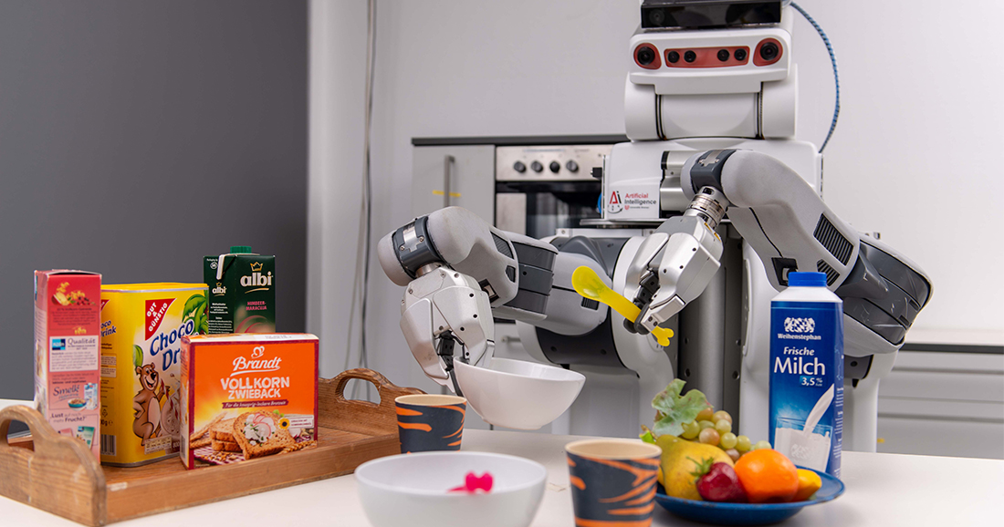 A robot holds a spoon and a bowl. In front of him is a table with cornflakes, milk, fruits and more.