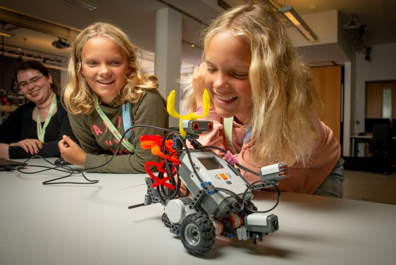 Girls are testing a little robot and they smile.